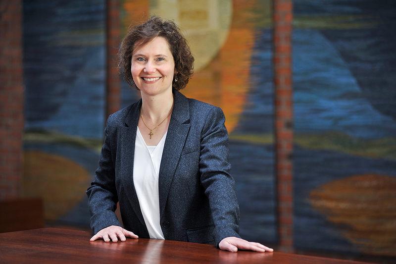 Pastorin Barbara Hoffmann-Fette steht am braunen Altartisch der Wicherngemeinde