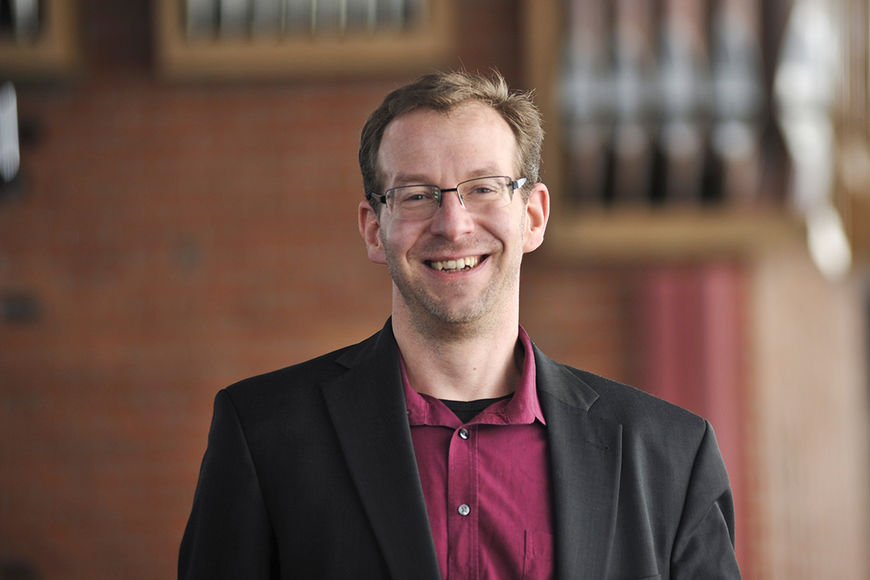 Kirchenmusiker Sven Farnick - Im Hintergrund sieht man undeutlich die Orgelpfeifen der Wicherngemeinde - Copyright: Ev.-Luth. Johann-Hinrich-Wichern-Kirchengemeinde zu Lübeck