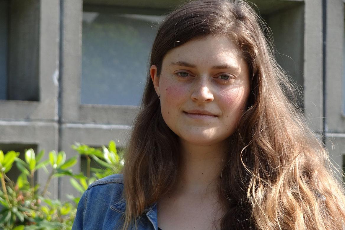 Portraitbild Jugendmitarbeiterin Henriette Peters steht vor der Kirche. Sie hat langes, braunes, welliges Haar - Copyright: Ev.-Luth. Johann-Hinrich-Wichern-Kirchengemeinde zu Lübeck
